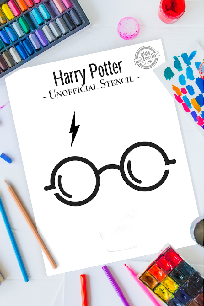 Harry Potter stencil pattern of Harry Potter glasses and lighting bolt scar, sitting on a table surrounded by art and craft supplies like coloring pencils, pastels, scrap paper with paint brush strokes in many bright colors, and little jars of paint.