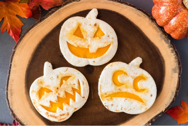 Three jack-o-lantern quesadillas with pumpkins in the background.