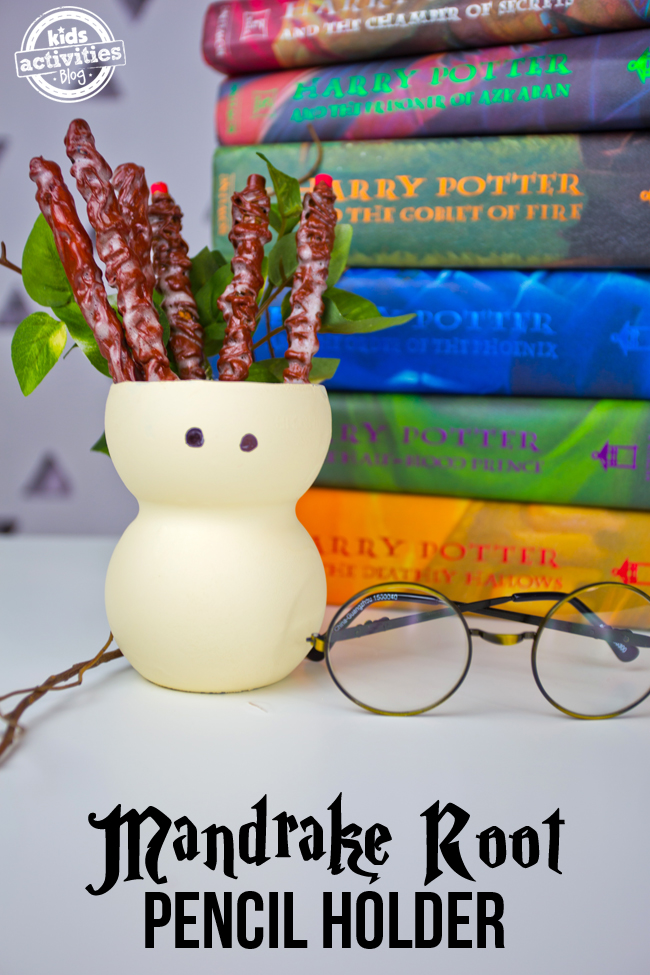 Harry Potter mandrake root pencil holder that is holding pencils on a white table next to Harry Potter stacked books, round glasses