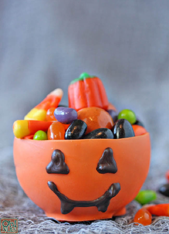 Pumpkin candy cup filled with various Halloween candy on a gray background.