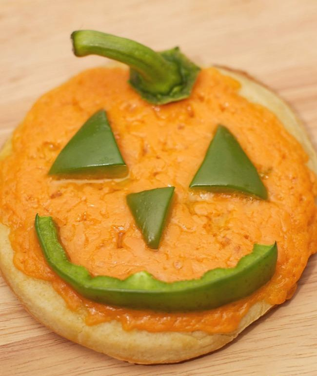Jack-o-lantern cheese pizza with peppers.