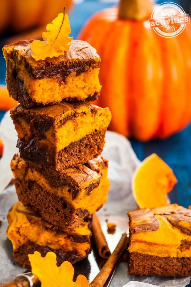 Cream cheese brownies stacked with fall leaves on top and a pumpkin in the background.