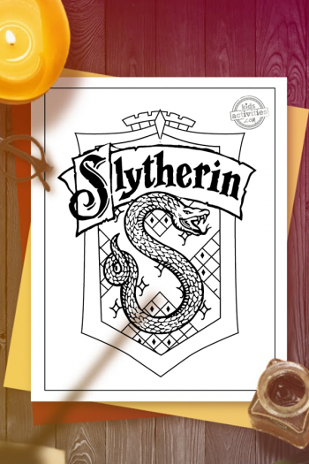 slytherin house crest coloring page on a dest with Harry Potter style glasses, candle, inkpot and quill with the shadow of someone waving a magic wand