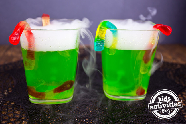 Two cups of green fog drinks with gummy worms coming out of them.