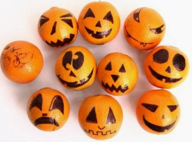 A group of oranges with various Halloween faces drawn on them on a white background.