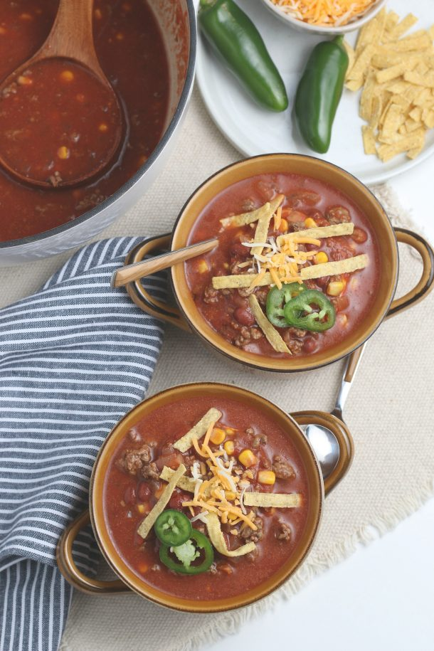Taco Soup Recipe - Easy Dinner Idea the Entire Family Loves - shown is two bowls of Taco soup next to a pot with serving spoon