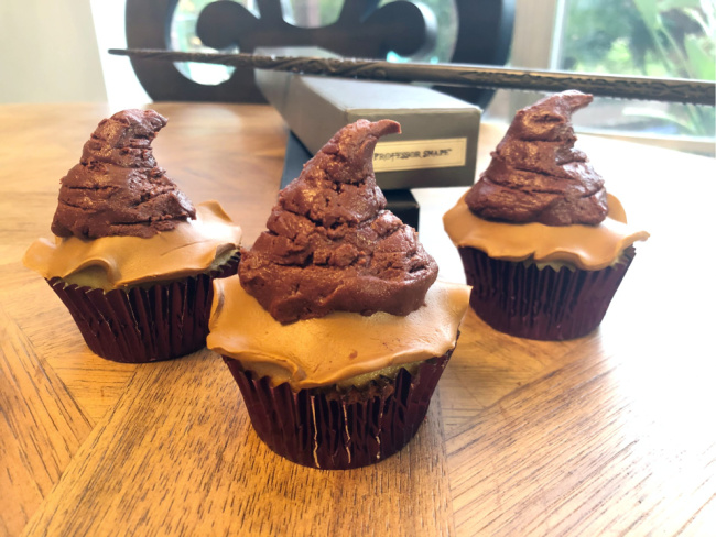 Harry Potter Sorting Hat cupcakes in purple metallic cupcake liners on a wooden table. Wand boxes in background with a wand resting on top of them.