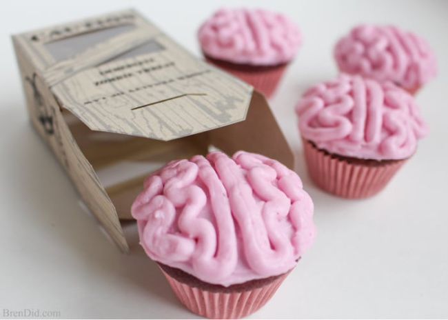 Zombie brain cupcakes with pink icing and pink cupcake liners coming out of a cardboard box on a white background.