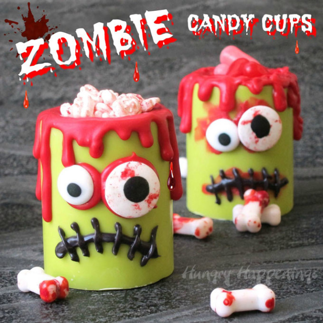 Green zombie candy cups with white candy bones on a gray background.