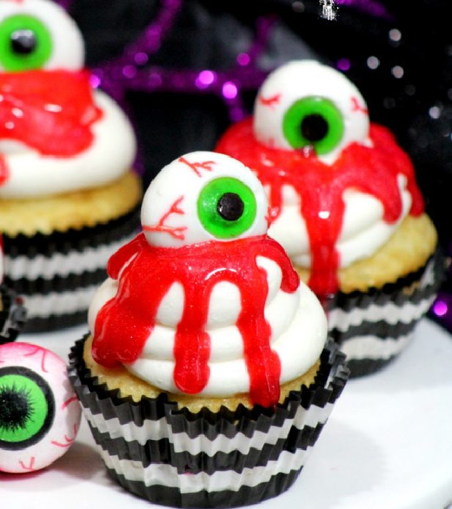 Zombie eyeball cupcakes in black and white striped cupcake liners on a white plate with a purple background.