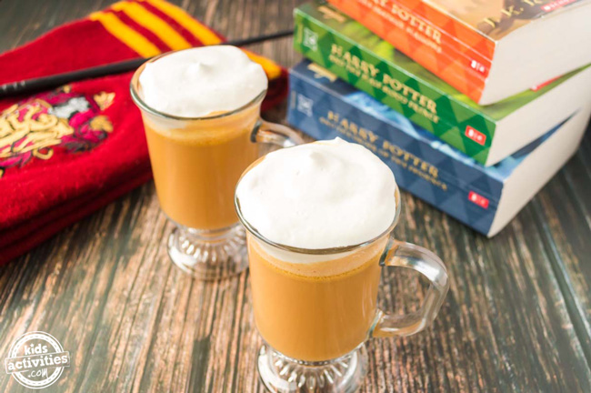 Harry Potter butterbeer in glasses on a wooden table with a Gryffindor scarf, wand, and Harry Potter books next to it.