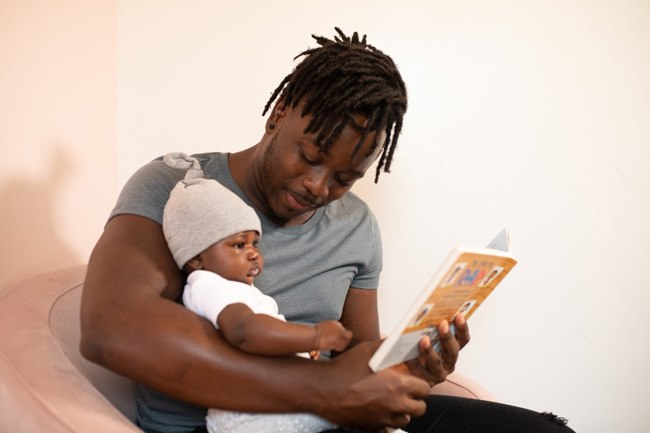 An african american dad reads a children's book to his infant daughter while sitting in a pink chair.