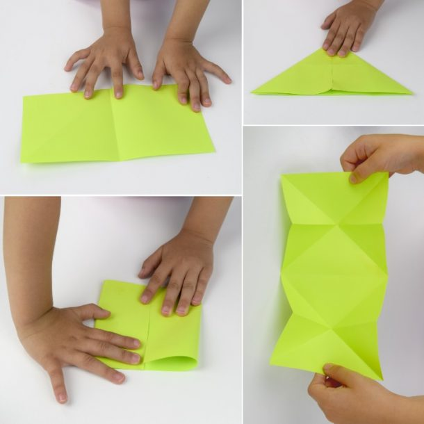 Green paper being folded by little hands in half, a triangle, the a diamond before it is opened up.