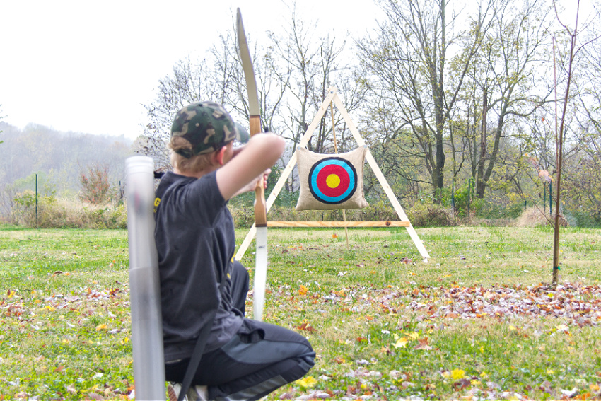 a boy aiming a bow and arrows at a handmade archery stand