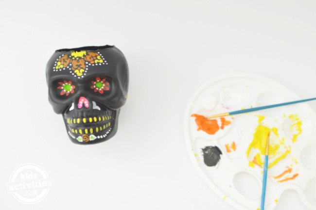 a black hollow skull with painted design to use as garden pot decoration for day of the dead with paint palette on the side