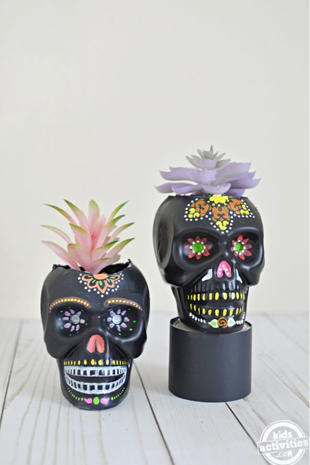 Beautiful black sugar skull planters with colorful paints and designs with fake succulents in them.