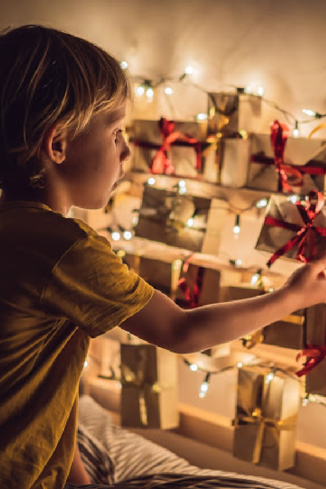A child chooses a gift box from a wall covered in christmas lights. Their home made advent calendar is cute, and memorable.