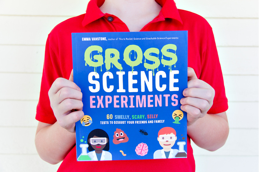 boy holding the book Gross Science Experiments by Emma Vanstone