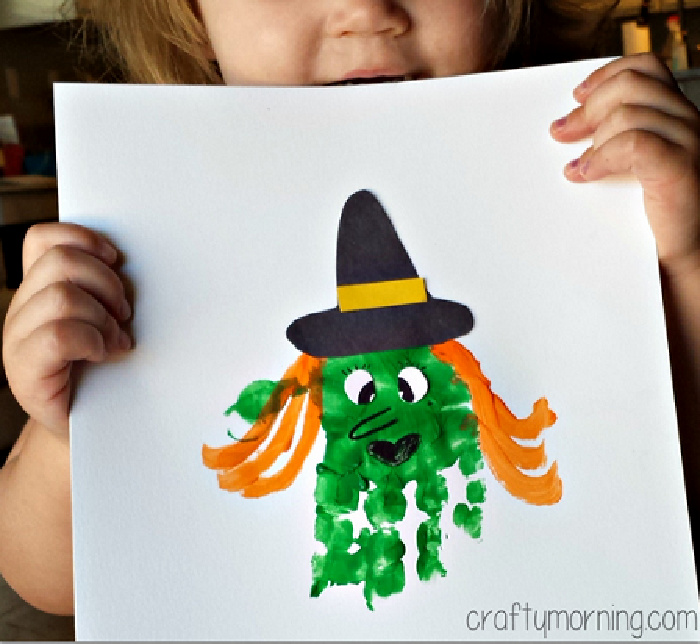 handprint halloween witch with a black witch hat and green handprint face