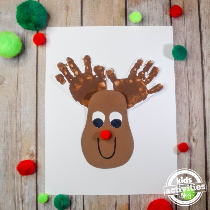 Rudolph the red nosed reindeer has handprint antlers and a pom pom nose