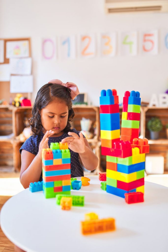 Kindergarten Activities for Learning and Play - Kids Activities Blog - kIndergartner playing with building blocks