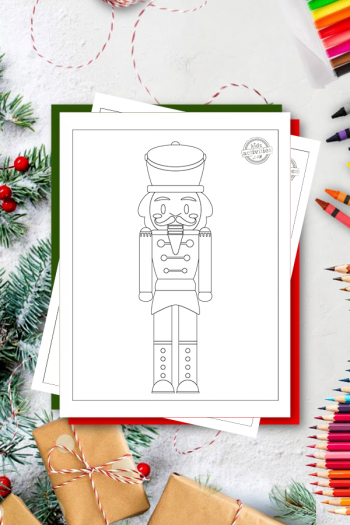 Nutcracker coloring page featuring a large nutcracker soldier on a white surface with Christmas presents and Christmas tree branches, coloring pencils, crayons and markers around it
