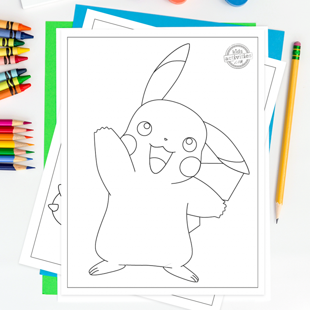 Pikachu Pokemon coloring pages on a desk surrounded by coloring pencils, crayons, paints and pencils. Coloring page with Pikachu waving hello on top.