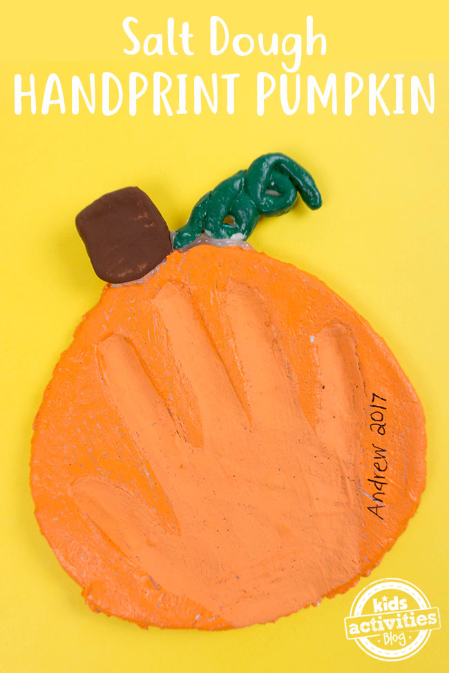 handprint in a salt dough pumpkin which is orange with a brown stem and green leaf