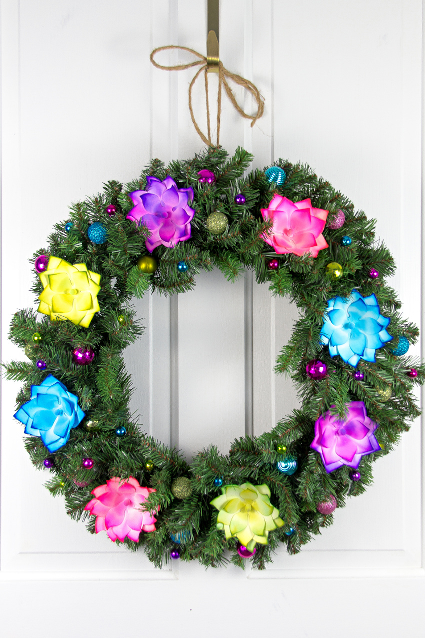 A Christmas wreath with brightly colored flowers and baubles.