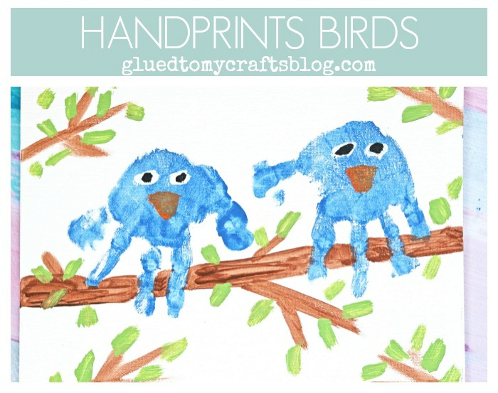two handprint blue birds sitting on a branch
