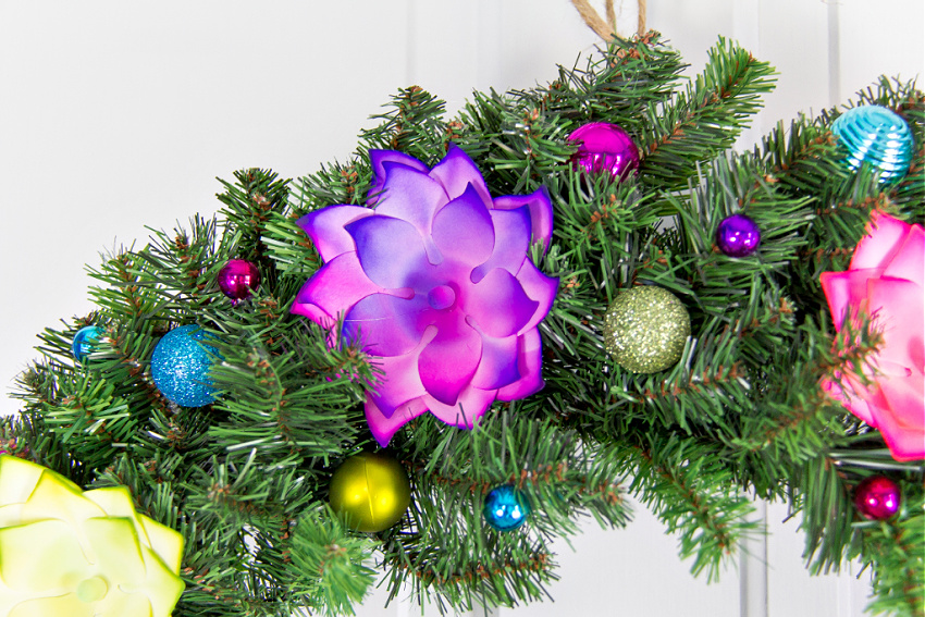 bright colored baubles and flowers glued to a plain Christmas wreath.
