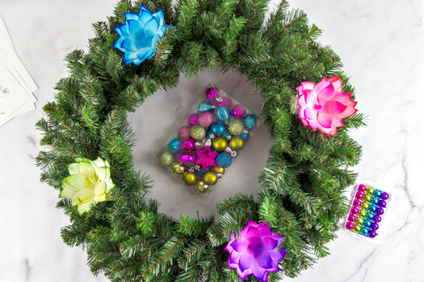 A green holiday wreath being decorated with bright flowers and baubles.