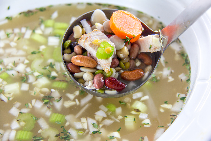 a ladle filled with beans, turkey and vegetables from a slow cooker