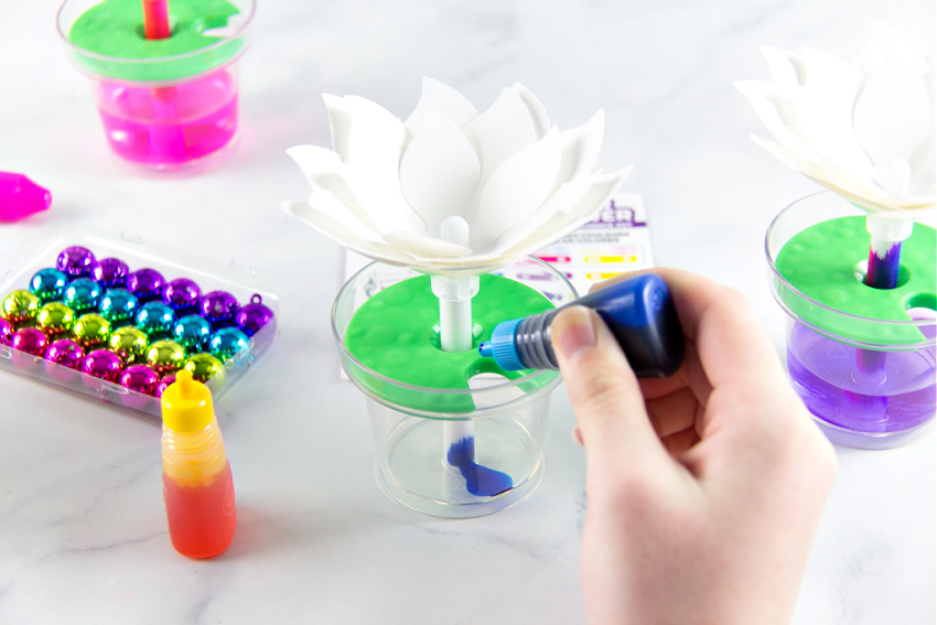A child adding dye to a paper flower color changing kit.