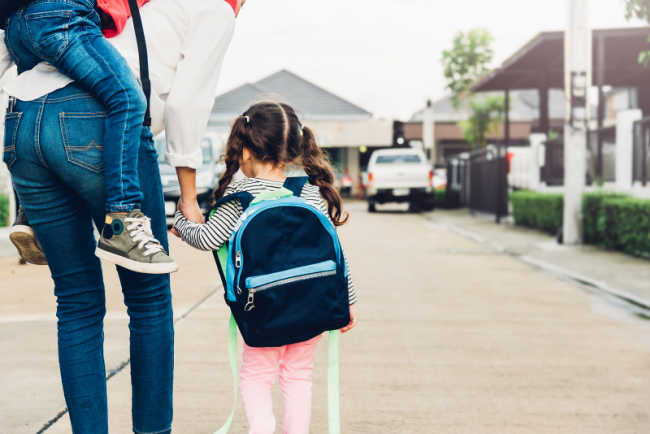 getting ready for kindergarten - child walking to classroom with parent holding hand