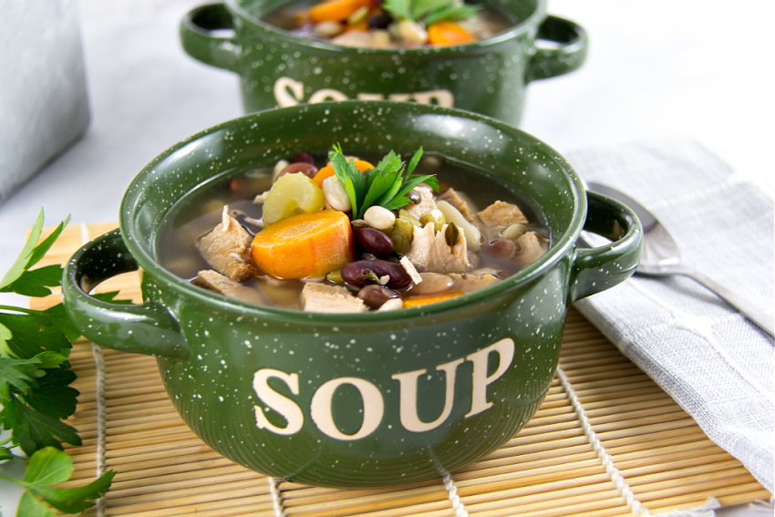 green soup bowls with handles filled with turkey and bean soup