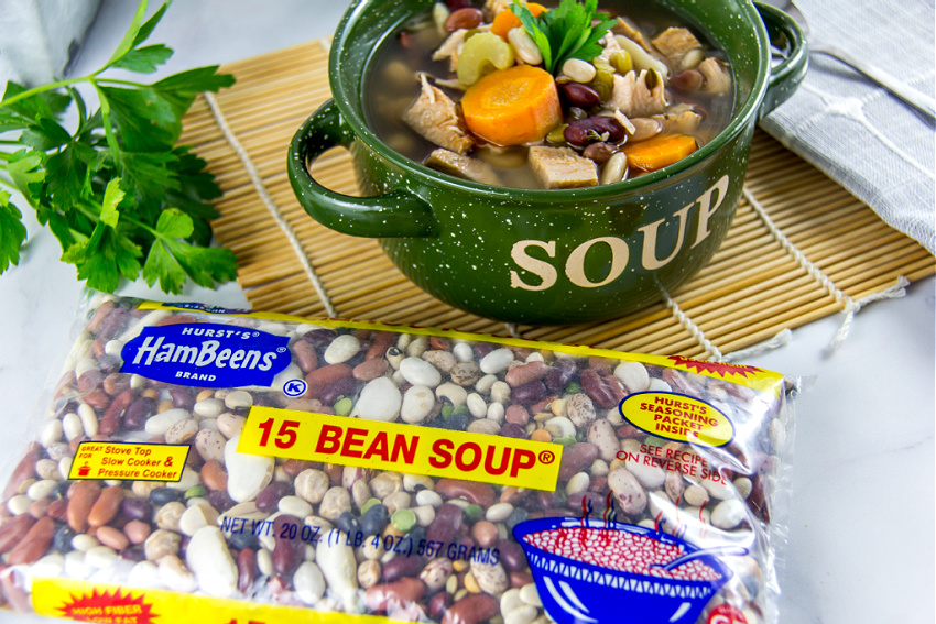 A bag of Hurst's 15 bean soup mix with a bowl of turkey, vegetable, and bean soup.