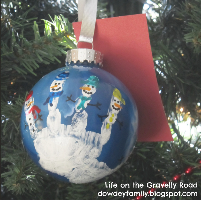 handprint snowman family ornament hanging in a Christmas tree