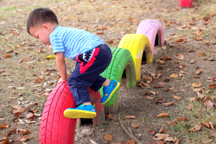 physical development 2 year old - boy jumping over tires outside with colorful tires - red, green, yellow and pink