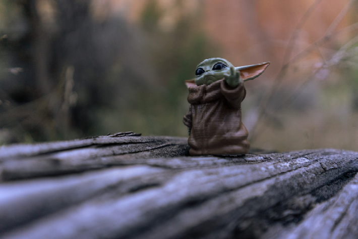 Baby Yoda toy outside for fun - Baby Yoda crafts, activities, art and more from Kids Activities Blog
