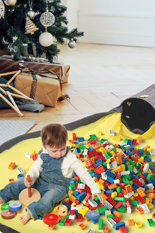 Child is playing with legos on a storage play mat with a christmas tree in the background and more presents waiting to be opened.