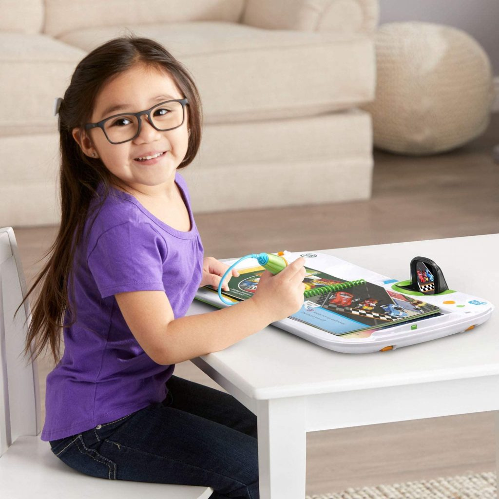 a little girl learns to read using a book about race cars and her leapfrog leapstart 3d!