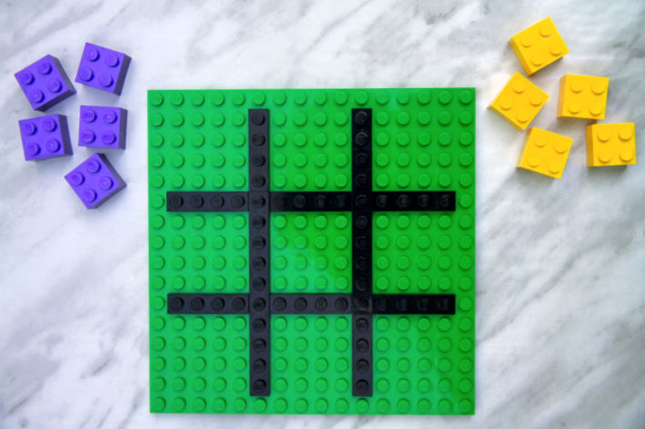 LEGO tic tac toe from Kids Activities Blog - pictured is green lego base piece with black board and purple and yellow bricks for game pieces