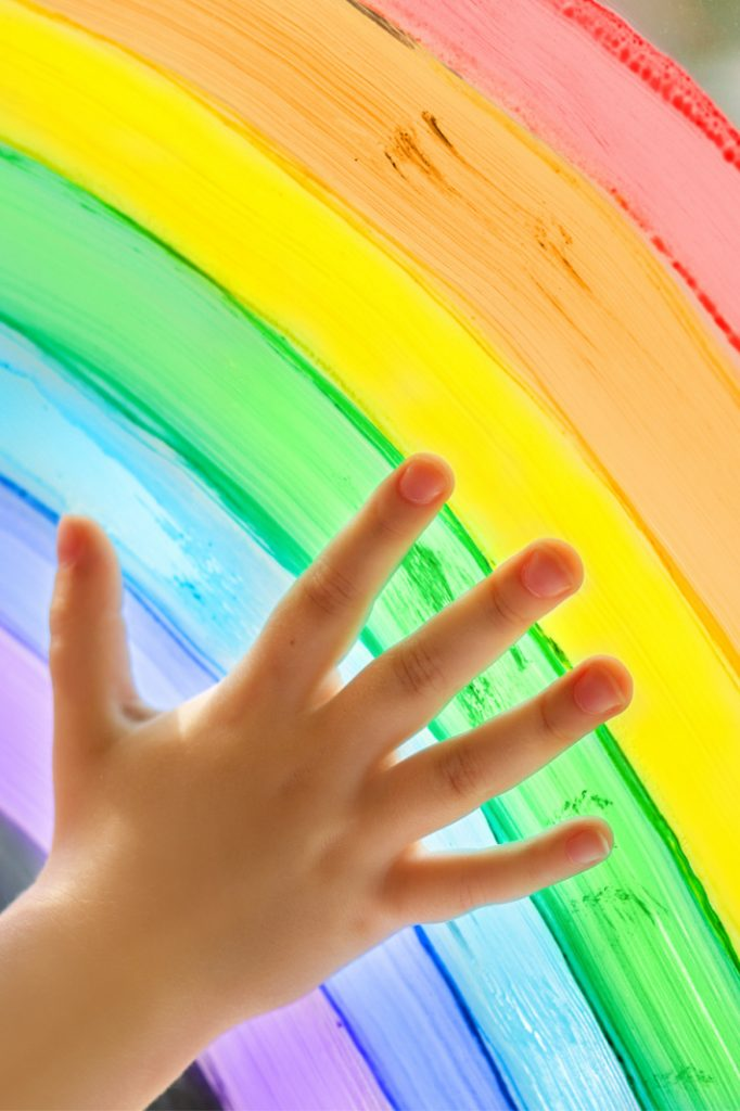all things rainbow from rainbow printables to rainbow party ideas from Kids Activities Blog - child's hand on a rainbow in a window