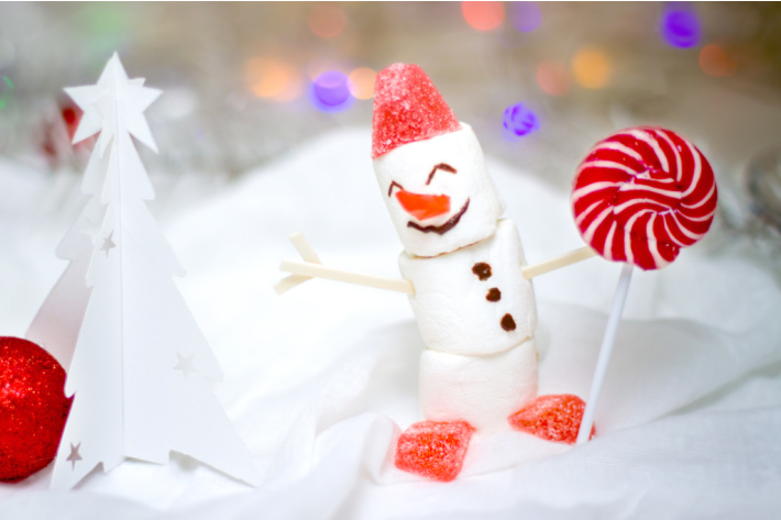 marshmallow snowman with gum drop hat holding a lollipop - Kids Activities Blog
