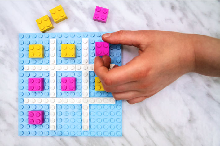 child playing tic tac toe on homemade LEGO brick board winning with pink piece placed in upper right corner