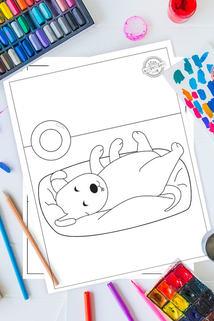 printable puppy coloring pages - printed pdf of puppy coloring page shown - little puppy sleeping on back surrounded by coloring items like crayons and colored pencils