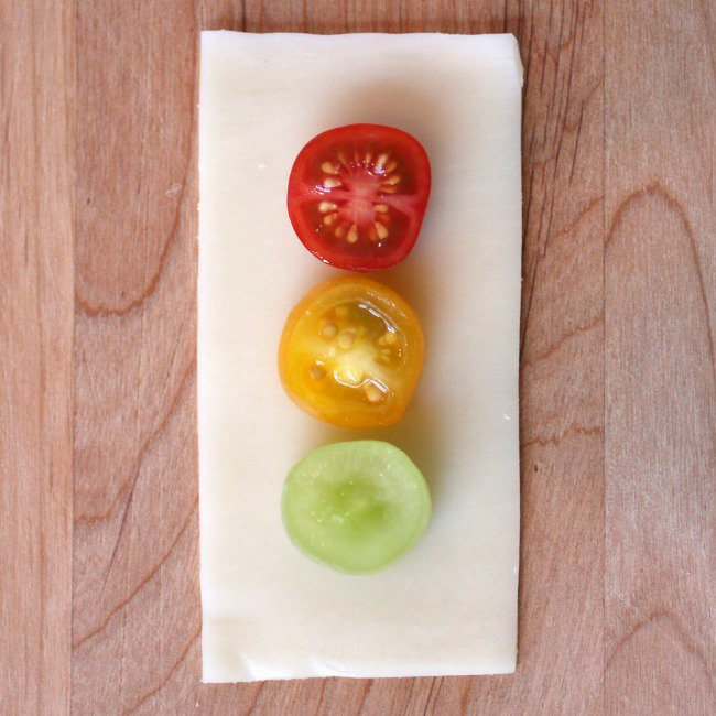 Traffic signal snack - inspired by a traffic light, this snack has three tomatoes in red, yellow and green colors on a slice of cheese on a cutting board
