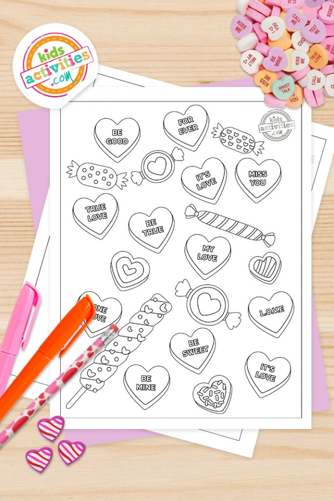 valentine heart coloring pages - printed version of the conversation heart coloring page on a desk surface with markers and a conversation heart candies