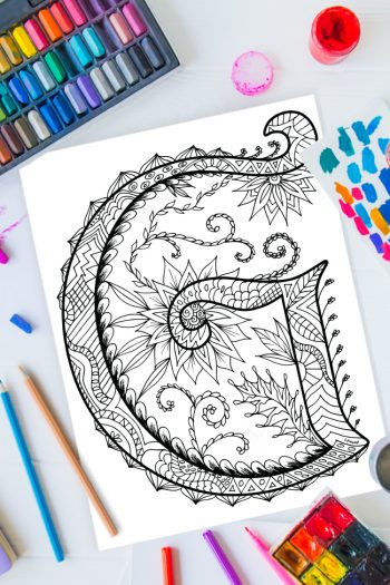Zentangle alphabet coloring pages - letter g zentangle design on background of paint, colored pencils and art supplies